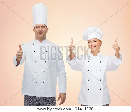 cooking, profession, gesture, teamwork and people concept - happy chefs or cooks couple showing thumbs up over beige background