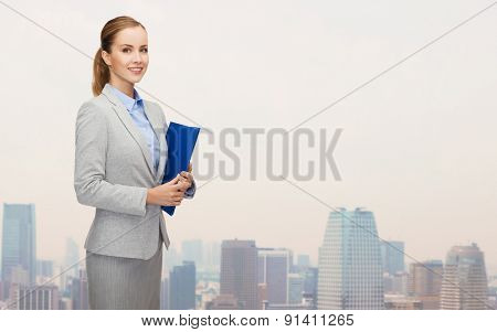 business, people and education concept - smiling young businesswoman with holding over city background