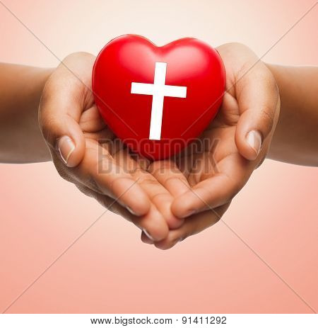 religion, christianity and charity concept - close up of female hands holding red heart with christian cross symbol over beige background