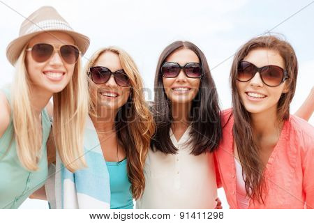 summer holidays, vacation and beach activities - girls in shades having fun on the beach