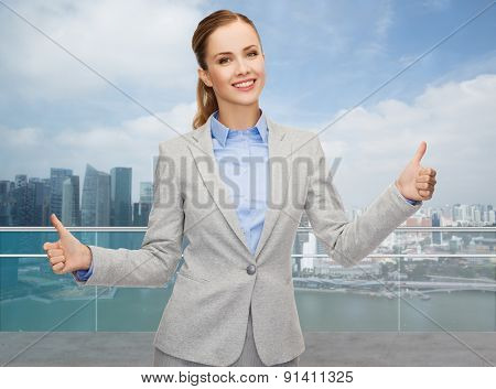 business, education, gesture and people concept - smiling businesswoman showing thumbs up over city background