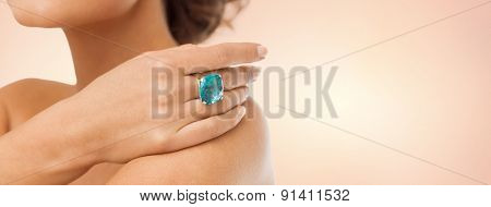 beauty, jewelry, people and accessories concept - close up of woman with cocktail ring on hand over beige background