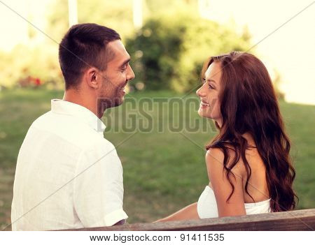 love, dating, people and friendship concept - smiling couple sitting on bench and looking to each other in park