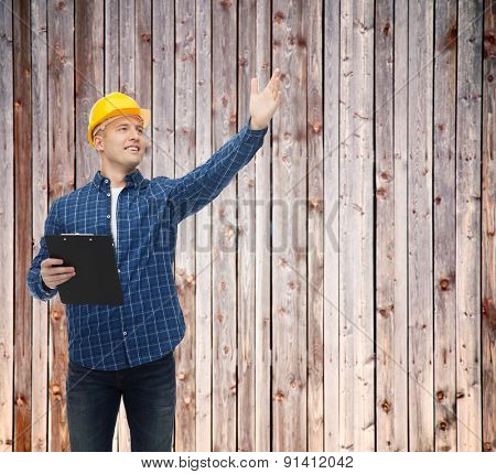 repair, construction, building, people and maintenance concept - smiling male builder or manual worker in helmet with clipboard pointing hand over wooden fence background