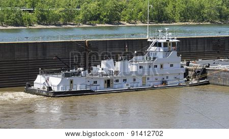 White Barge with No Markings or Insignia on a River with a Lock Wall.