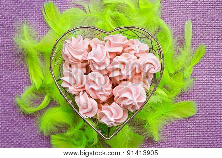 Pink Meringue In Heart Shape Basket Surrounded By Bright Green Feathers, On Purple Background, Top V
