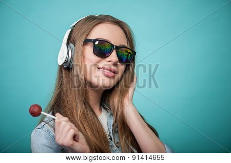 Cheerful Hipster woman with headphones and candy