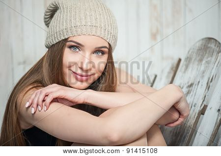 Beautiful hipster woman is sitting near white wall