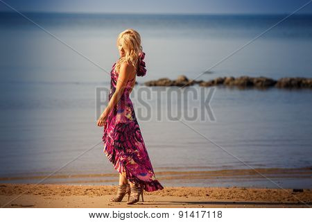 Blonde Girl In Purple Dress Walks On Beach