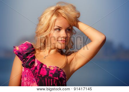 Portrait Of Blonde Girl In Red Against Sea