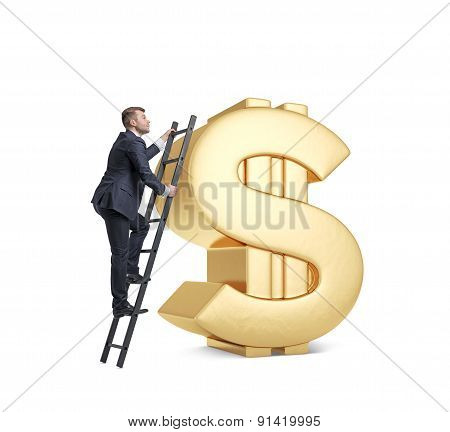 Businessman Is Climbing On The Huge Golden Dollar Sign. Isolated.