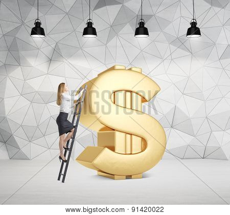 Young Lady Is Climbing On The Huge Golden Dollar Sign In The Room. Four Black Ceiling Lamps.