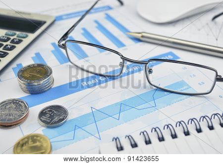 Glasses, Coin And Pen On Financial Chart And Graph, Investment Concept