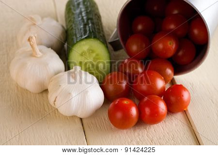 Several Cherry Tomatoes And Garlic With Cucumber On White Board