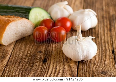 Single Garlic Head In Front Of Other Vegetable And Baguette
