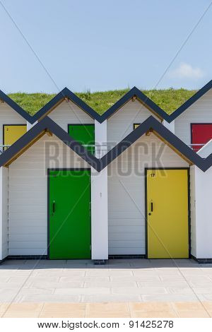 Colourful Doors Of Yellow And Green, With Each One Being Numbered Individually, Of White Beach House