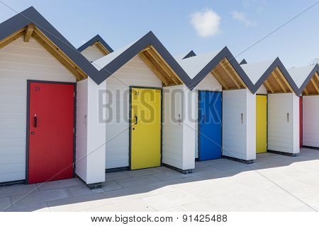 Colourful Doors Of Blue, Yellow And Red, With Each One Being Numbered Individually, Of White Beach H