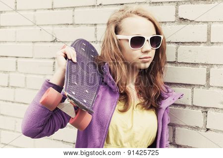 Blond Teen Girl In Sunglasses Holds Skateboard