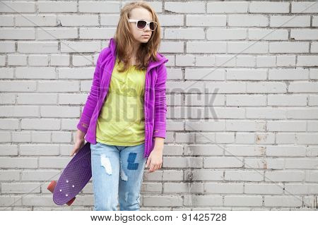Teenage Girl In Jeans And Sunglasses With Skateboard
