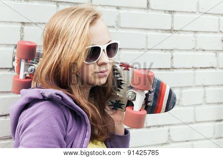 Blond Teenage Girl In Sunglasses With A Skateboard