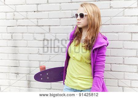 Blond Teenage Girl In Sunglasses Holds Skateboard