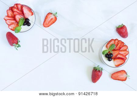 Summer sweet dessert food panna cotta in glass with empty frame for lorem ipsum design text and stra