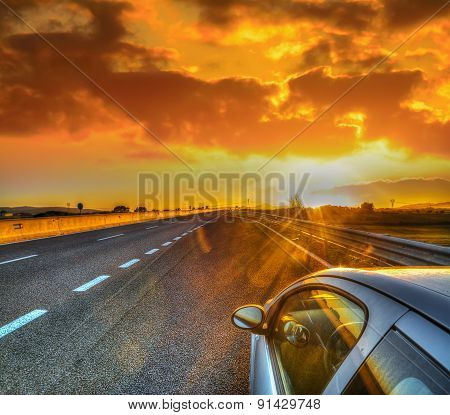 Car On The Edge Of The Road Under A Scenic Sky At Sunset