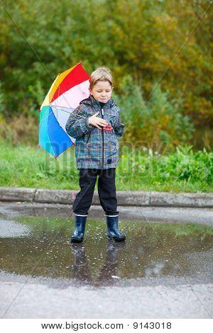 Cute Boy Outdoors At Rainy Day