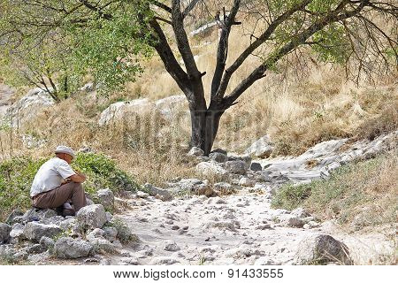 Ukraine, Bakhchisaray - September 06, 2011: A Man Playing On A Pipe Sitting On The Tourist Trail. Cr
