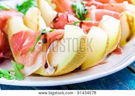 Salad Of Melon With Thin Slices Of Prosciutto, Arugula Leaves And Balsamic Sauce Closeup