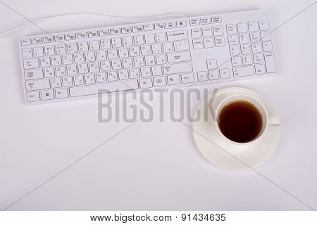 White keyboard and coffee cup