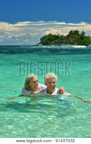 Loving elderly couple bathing in the sea