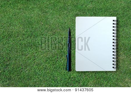 Notebook And Pen On Grass Texture