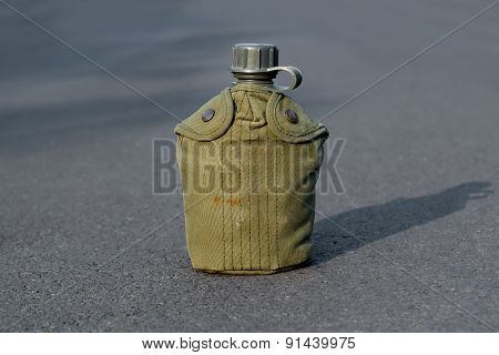 Army water canteen on the road