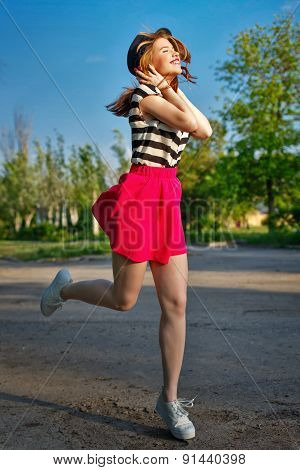 Girl Running Holding A Hat.
