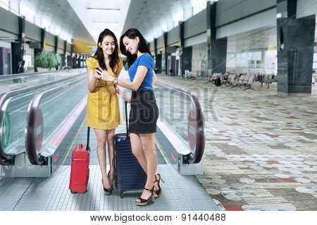 Female Travelers With Cellphone In Airport