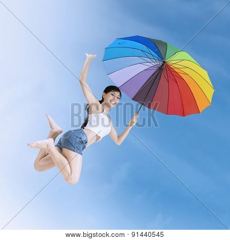 Girl Leaps With A Colorful Umbrella Outdoors