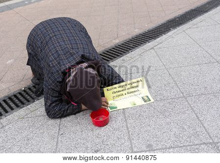 Beggar Lying On The Ground