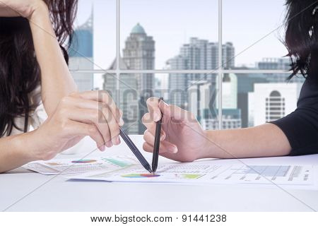 Two Businesswomen Pointing At Financial Graph