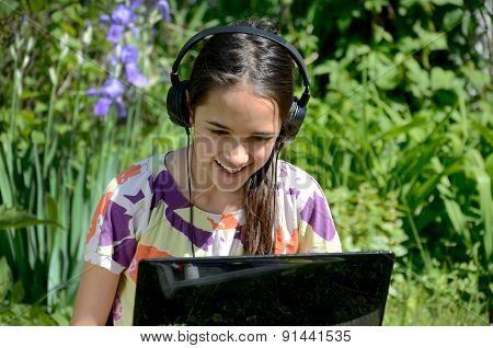 Little Girl Uses a Laptop in the Garden