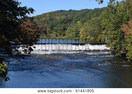 Scenic river and waterfall with trees in Fall in Rhode Island