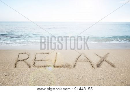 Relax Word Handwritten In Sand On Sunny Beach