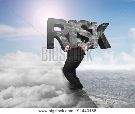 Man Carrying Risk Concrete Word On Ridge With Cloudscape Cityscape