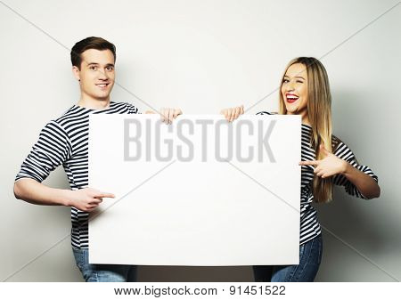 Lovely couple holding a banner -  over a gray background