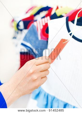 Woman's Hand Choosing Child Dress At Clothing Store.