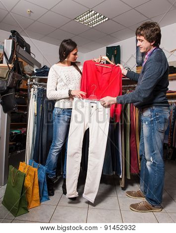Shop Assistant Showing Jeans And Shirt To Beautiful Woman