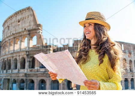 Smiling Woman Holding Map Of Rome At Colosseum In Rome