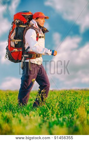 Hiker with backpack walking in the field