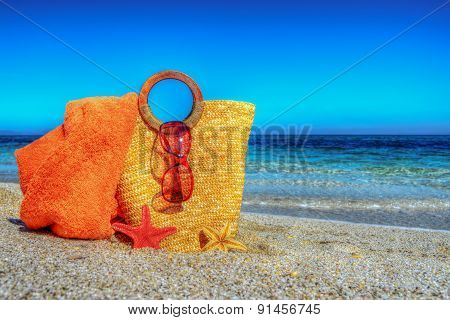 Straw Bag, Beach Towel And glasses On The Sand