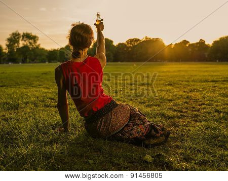 Woman Lifting Bottle To Sunset In Park
